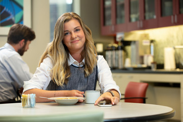 Young Caucasian woman looking at camera with a smile, while sitting in break area of office with lunch of soup and Hot Tea
