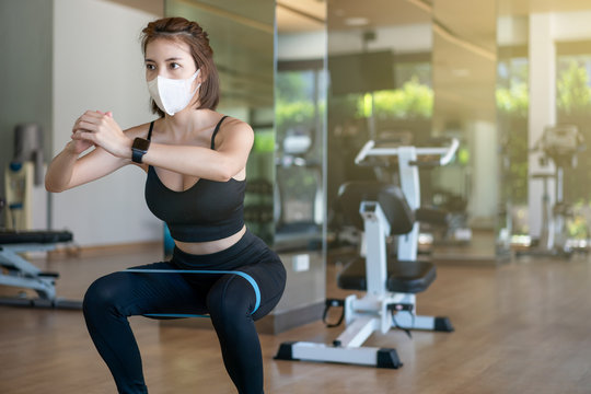 Woman wearing face mask, doing squat with booty equipment stretching strap in a fitness center. during corona virus pandemic.