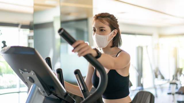 Woman wearing face mask, using an elliptical machine in a fitness center. during corona virus pandemic.
