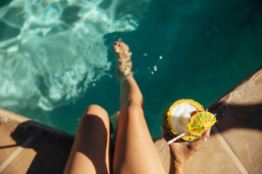 A woman holds a tropical pineapple drink poolside at a resort
