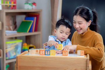 Asian student in preschool use a letter box make a study word in class room with his teacher