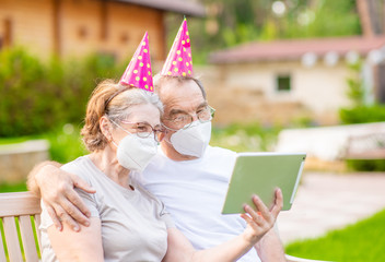 Senior couple wearing party's caps and protective masks celebrates  birthday with her family on video call during the coronavirus epidemic