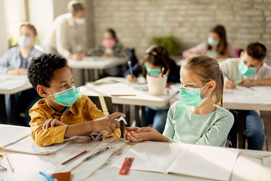 Two classmates with face masks sharing hand sanitizer in the classroom.