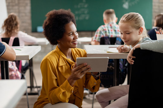 Happy black teacher and schoolgirl using digital tablet in the classroom.