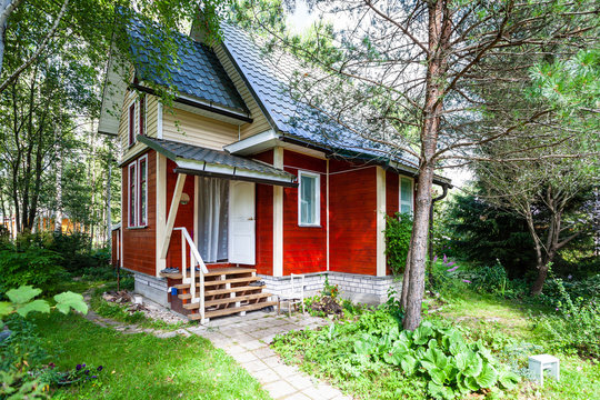 one-storey wooden country house with attic in Russia in summer