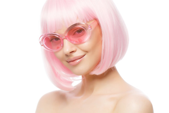 Young funky girl standing with naked shoulders, wearing pink short wig and plastic eyeglasses, ready for party, isolated on white background