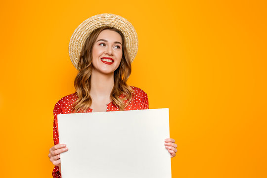 Happy caucasian girl in red dress with red lips wearing straw hat smiling and holding white blank A3 poster with copy space