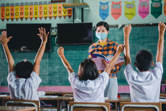 Young Asian female teachers wearing a medical face and students in a rural Thai village school are learning, grinding and raising their hands to answer teacher questions.