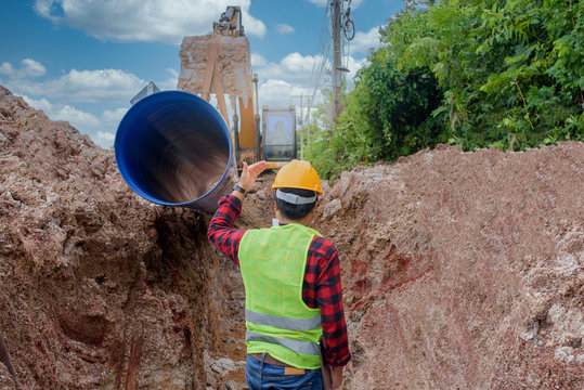 A young Asian engineer is inspecting a large sewer that is buried underground at a construction site. The excavator is empty the water pipe.