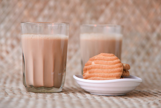 Top view of Indian Masala Chai and biscuit, traditional milk tea beverage with milk and spices Kerala India. Two cups of organic ayurvedic or herbal drink India, good in winter for immunity boosting.