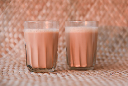 Top view of Indian Masala Chai or traditional milk tea beverage with milk and spices Kerala India. Two cups of organic ayurvedic or herbal drink India, good in winter for immunity boosting.
