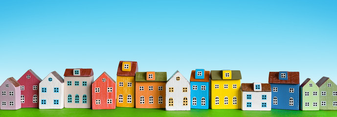 Row of wooden miniature colorful retro houses on blue background