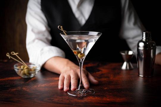bartender serving martini in glass at bar