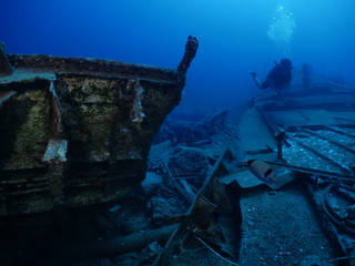 Acrylic Prints Shipwreck scuba divers exploring shipwreck scenery underwater ship wreck deep blue water ocean scenery of metal underwater and fish around