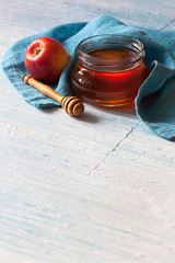 Rosh Hashanah holiday, greeting card, background with honey jar, apple and blue kitchen towel on wooden table