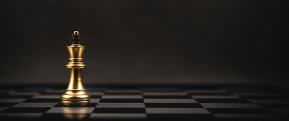 King golden chess standing on chess board concept of business strategic plan and professional organization management leader.