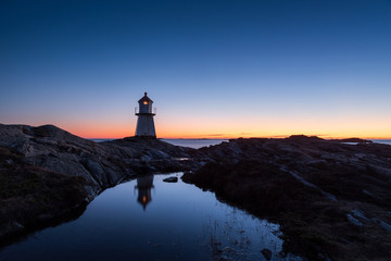 Lighthouse surrounded by rocks at night, lighthouse with lights on at sunset