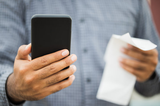 Businessman using holding smartphone and bills of payment per month. Financial buying payment income expenditure pay phone bills.
