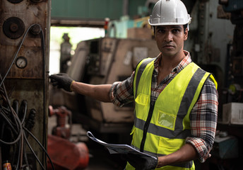 Portrait of young handsome technician man or industrial worker with hard hat or helmet and vest jacket working electronic machinery and mechanical engineering in Factory of manufacturing place