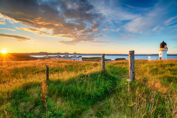 Wall Mural - Beautiful sunset over the lighthouse and coastguard cottages at Arnish Point