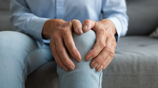 Close up mature old woman touching knee joint, having painful feelings. Unhealthy middle aged senior female retiree suffering from arthritis, bones disease osteoporosis or inflammation processes.