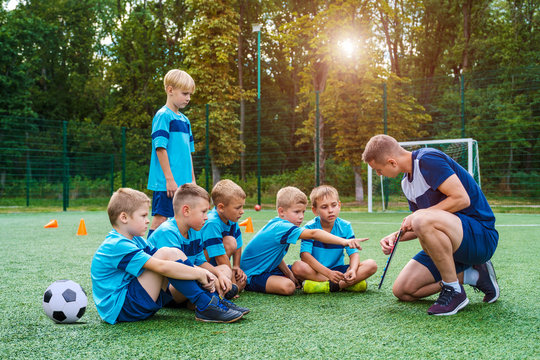 Young coach with clipboard teaches little children the strategy of playing on the football field.