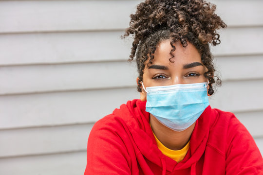 African American female young woman wearing face mask in Coronavirus COVID-19 pandemic