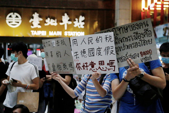 People hold up signs to show their support for the Thailand's youth pro-democracy groups that protest against Thai government, in Taipei