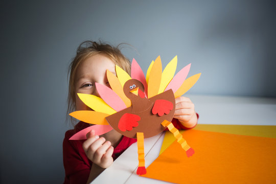 paper craft for kids. DIY Turkey made for thanksgiving day. create art for children. girl playing with a toy