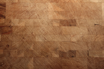 An horizontal close up of a used butcher's block with lots of knife marks and scratches