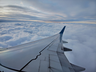 Clouds and sky as seen through window of an aircraft with airplane's wing Fotobehang