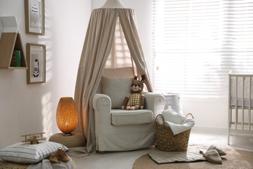 Stylish baby room interior with crib and comfortable armchair