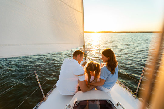 Family Yacht Sailing, Parents And Daughter Sitting On Deck, Back-View
