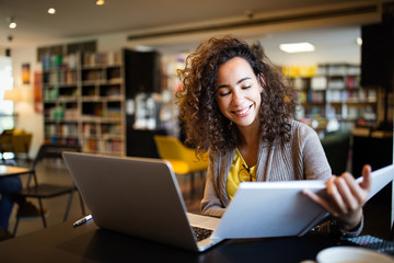 Young afro american woman sitting at table with books and laptop for finding information