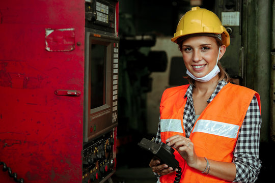 Young Woker Woman working with metal industial factory warehouse