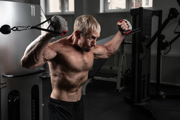 Muscular adult brutal man training on TRX loops in the gym. Portrait of caucasian authentic bodybuilder doing exercises in HIIT workout