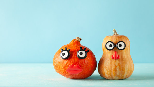 Funny pumpkins with faces on pastel blue background with copy space. Concept celebration of Halloween or Thanksgiving.
