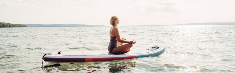 Middle age Caucasian woman practicing yoga on paddle sup surfboard. Female doing workout on lake water. Modern individual hipster outdoors summer sport activity. Web banner header for website.