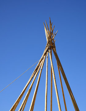 Teepee construction: raised poles are held togther by winding heavy rope around the tops.