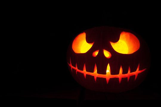 Ghastly Halloween pumpkin head jack lantern on black background