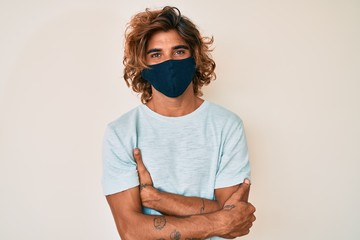Young hispanic man wearing covid-19 mask happy face smiling with crossed arms looking at the camera. positive person.