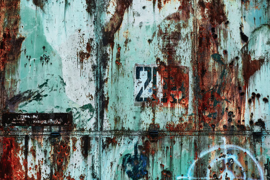 Grange metal wall with dull turquoise paint, rust, hunting target, bullet holes and number 203. Abandoned military hangar from Russia - ideal background for website about urban exploration