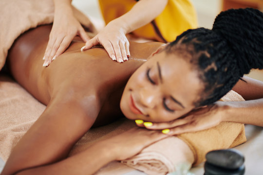 Close-up image of young African-American young woman getting spa body massage treatment in beauty salon