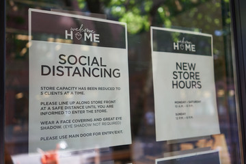 Social distancing guidelines are seen at the entrance to a retail business in Portland, Oregon, during a pandemic summer.
