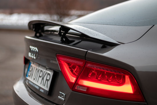 Cluj-Napoca, Romania -February 14, 2019 :Audi A7 brown metallic colour with chrome ornaments, isolated. Close up photo of open rear trunk spoiler, black privacy windows and chrome ornaments.
