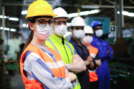 Industrial woman engineer or factory worker wearing helmet and hygiene face mask with men stand in line at manufacturing plant.People working industry during covid pandemic.
