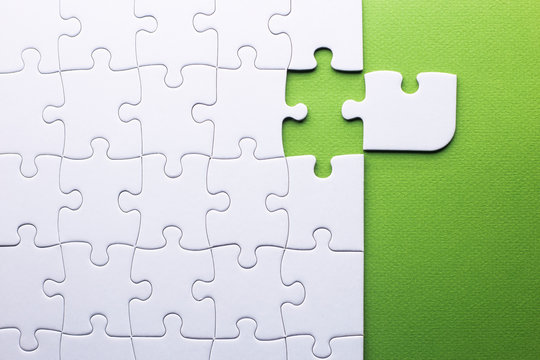 white puzzle with piece that does not fit on a green background
