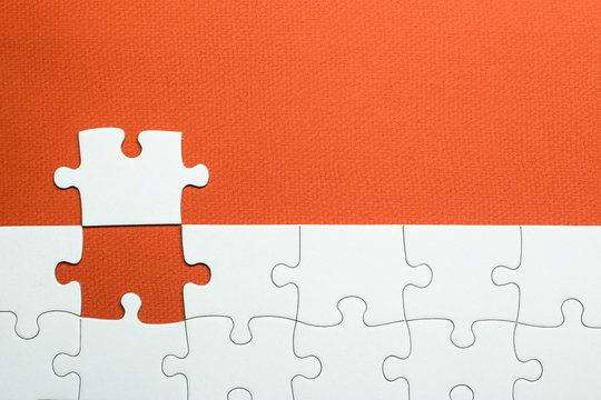 white puzzle with a piece that is not well positioned on an orange background
