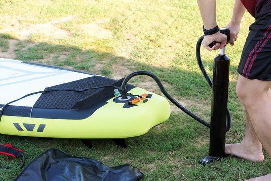 Man putting air into inflatable stand up paddle board