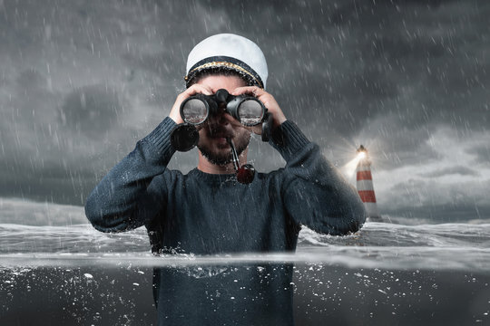 shipwrecked helmsman watching with binoculars the rock in the water and standing underwater